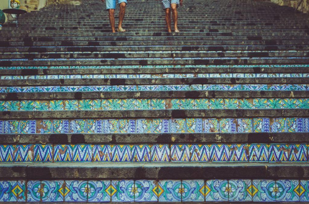 два человека ступают по лестнице, украшенную керамической плиткой.