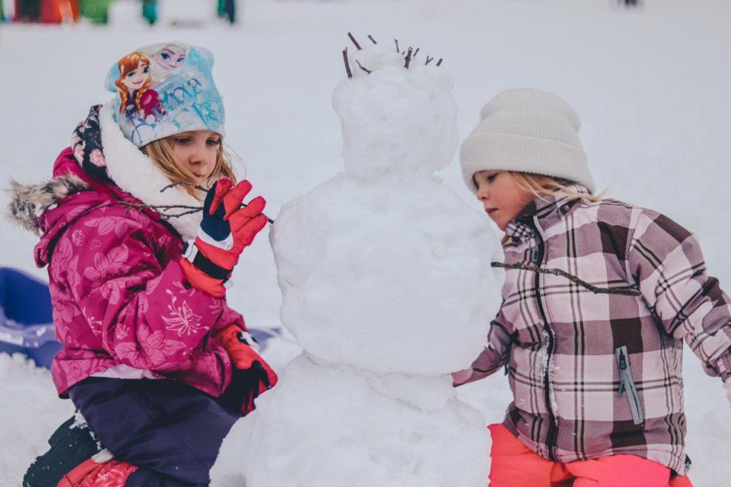 дети лепят снеговика в зимнюю снежную погоду